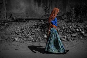 Woman with veil over head and long skirt walking