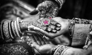 Hand with henna patterns on it with flower ring